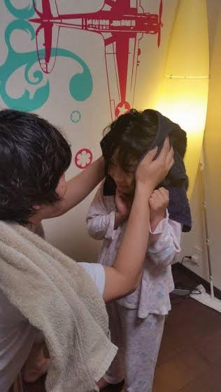 タオルで頭を拭いてもらう子供