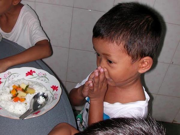 食事前に手をあわせる孤児