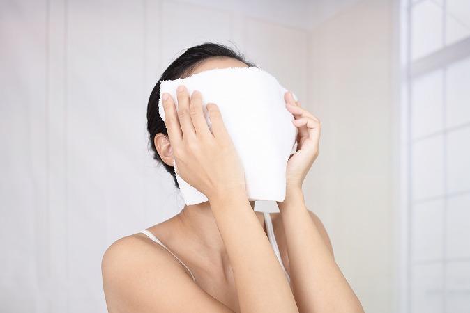 蒸しタオルで顔を覆う女性