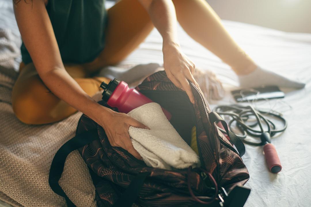 タオルをスポーツバッグから取り出している女性
