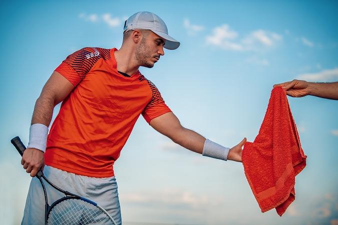 タオルを受け取るテニス選手